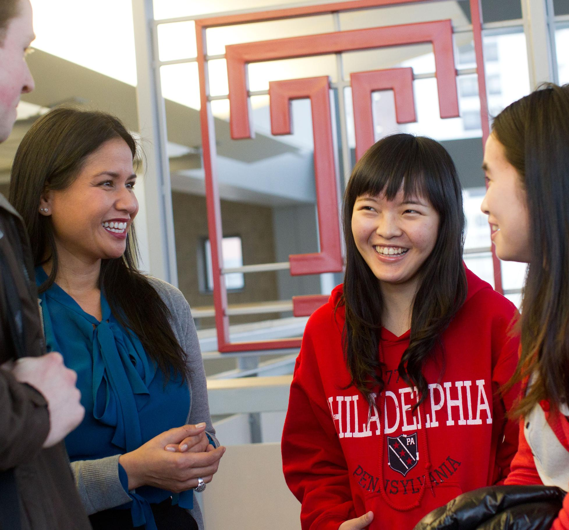 Four students gather to talk on campus