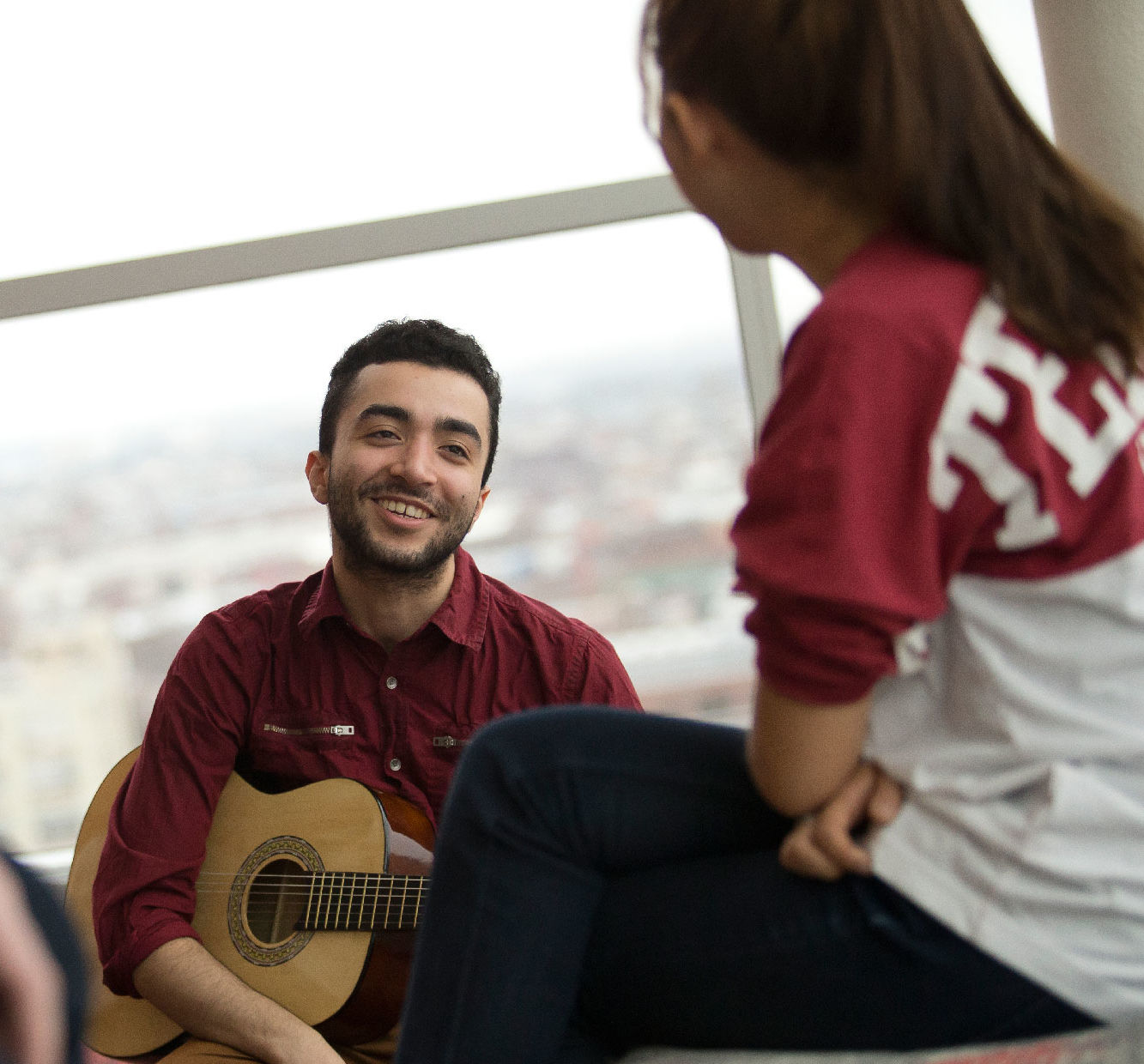 Student with guitar smiling