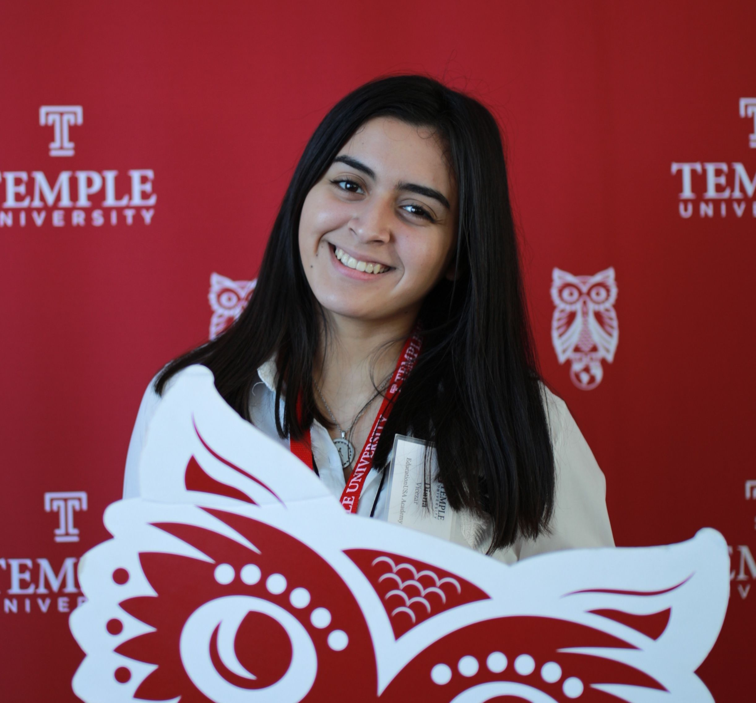 Diana Vicezar, an EducationUSA Academy student, holding an owl cutout and smiling